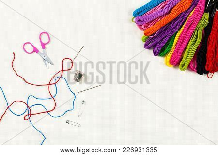 Embroidery Floss Background On A White Cloth. Concept For Sewing And Embroidery. Selective Focus.