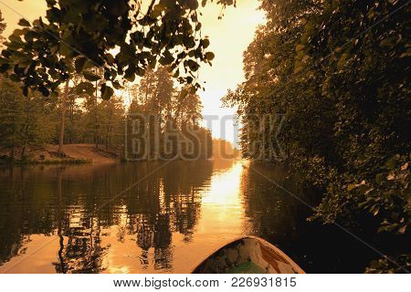 Forest Reflection With Boat On Lake Or River. Golden Hour, Orange Sunset Time.