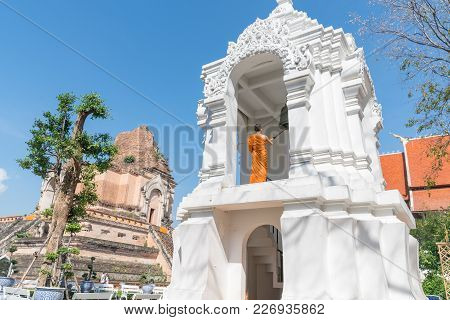 Chiang Mai Thailand - January 29 2018; Buddhist Monk Stands  On High Level Of White Ornate Bell Towe