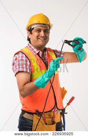 Indian Electrician Engineer In Action With Wire Cutter, Drilling Machine Etc, Standing Isolated Over