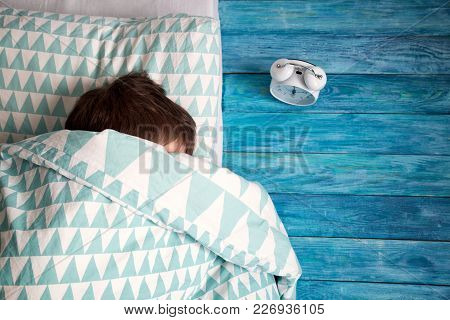 Eight Years Old Child Sleeping In Bed On Pillow. Boy Lying Blue Wooden Background Covered With Blank