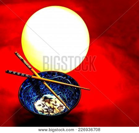 Fine Art With A Asian Bowl, Chopsticks, A White Lamp Ball On A Red Cloudy Background.