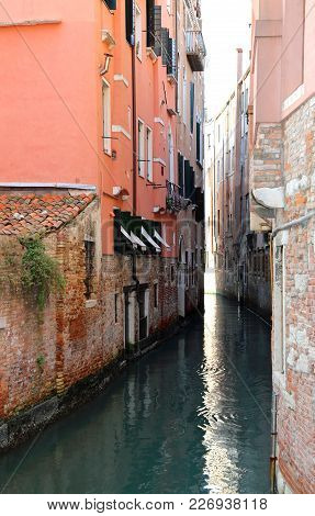 Narrow Canal With Old Houses With Low Tide In Venice Italy