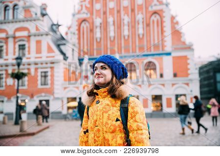 Riga, Latvia. Young Beautiful Pretty Caucasian Girl Woman Dressed In Yellow Jacket And Blue Hat Enjo