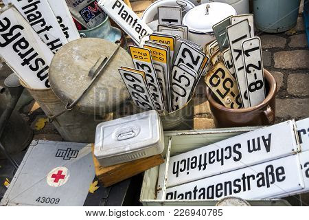 Berlin, Germany - October 23, 2016: Assorted License Plates And Street Signs And First Aid Kit  In F