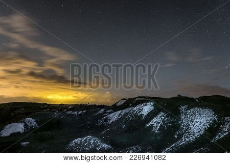 Night Landscape With Chalk Ridges Under Cloudy And Starry Sky. White Cretaceous Hills At Night. Natu