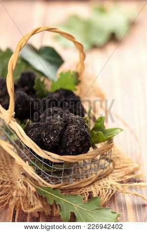 Black Truffles In Basket  On Old Wooden Table.