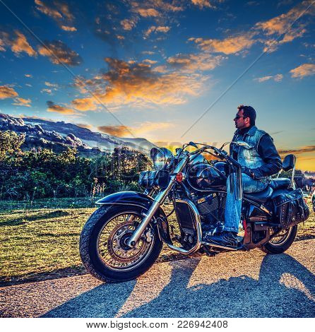 Biker On A Classic Motorcycle On The Edge Of The Road At Sunset