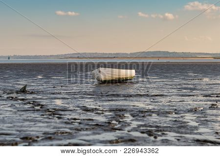 A Boat In The Oare Marshes With The North Sea Coast Of Kent In The Background, Near Faversham, Kent,