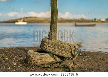 Old Tyres And A Wooden Post In The Oare Marshes Near Faversham, Kent, England, Uk - With Boats And T
