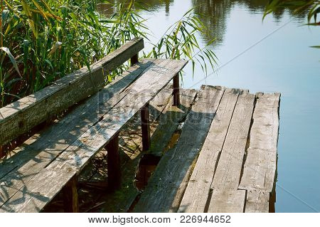 Old Park Bench By The Water, Broken Wooden Bench In The Forest For Tourists