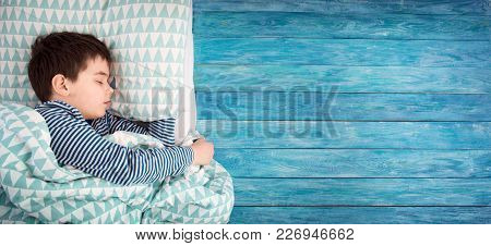 Eight Years Old Child Sleeping In Bed On Pillow. Boy Asleep On Wooden Background