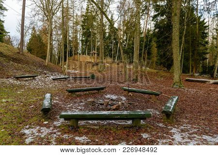 Camping And Resting Area By The River With Bench And Fireplace