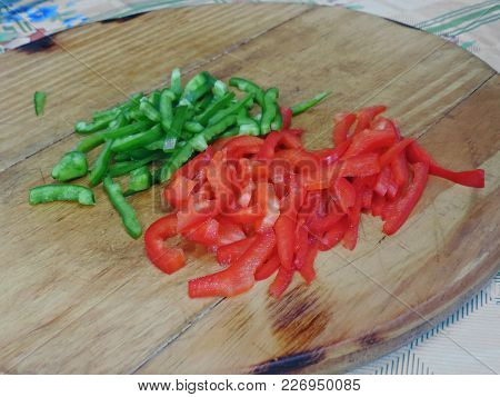 Green And Red Bell Peppers Sliced On A Wooden Board