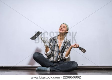 Happy Young Girl Sits On The Floor, Doing Repairs In Her New Apartment