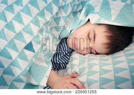 Eight Years Old Child Sleeping In Bed On Pillow. Boy Lying Covered With Blanket
