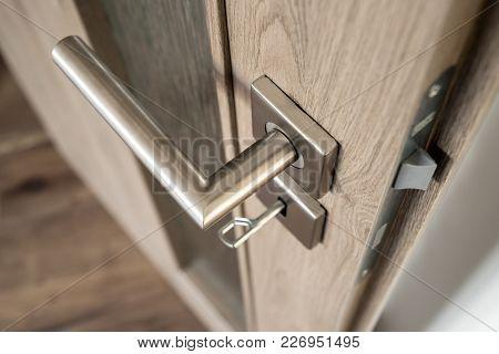 Silver Matte Door Handle On An Oak Wooden Door With Glass And Small Depth Of Field