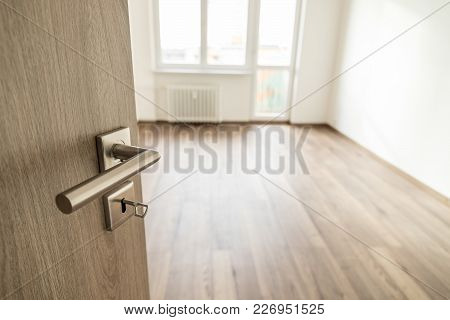 Opened Wooden Door With Silver Matte Handle Leading To An Empty Room After A Successful Reconstructi