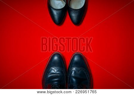 High Heels And Men's Shoes On An Intense Red Background