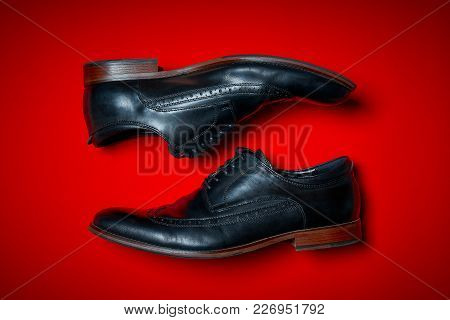 Top View Of A Pair Of Male Shoes On An Intense Red Background