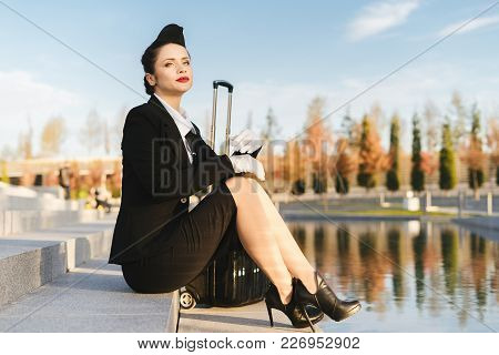 Attractive Young Woman Stewardess In Uniform Sits In Park With Suitcase And Waits For Her Flight