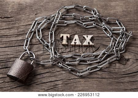 The Word Tax Next To The Chain And The Closed Lock On An Old Wooden Background.