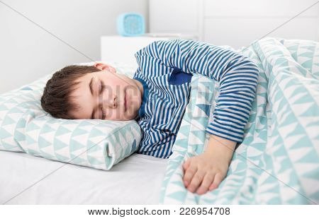 Eight Years Old Child Sleeping In Bed On Pillow. Boy Asleep In White Bedroom