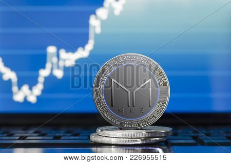 Physical Maker (mkr) Cryptocurrency; Silver Maker Coin On The Background Of The Chart