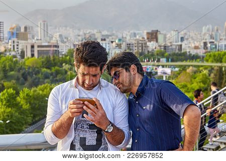 Tehran, Iran - April 28, 2017: Nature Bridge, Two Iranian Tourists Are Looking At The Smartphone Scr
