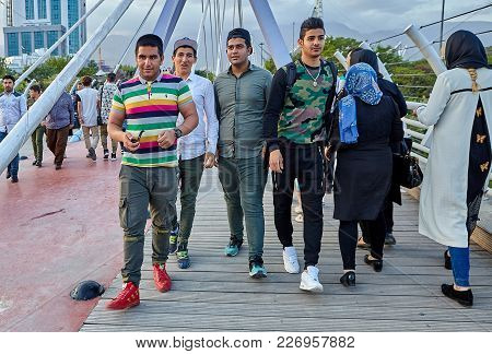 Tehran, Iran - April 28, 2017: Four Young Men Walk Along The Tabiat Bridge In A Crowd Of Other Peopl