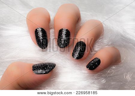 The Female Hand With Black Glittered Nails Is On White Furry Background.