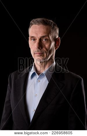 Portrait Of Serious Old Man Senior On Black Background Looking At Camera. Studio Shoot