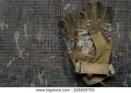 Very Used And Old Pair Of  Tactical Gloves Lies On A Multicam Background.