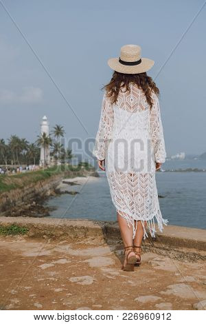 Girl In A Hat And A White Fishnet Cardigan Looks At The Ocean