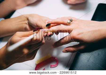 Gel Nail Extensions Build Up Process. Women At Beauty Parlour Doing Manicure.