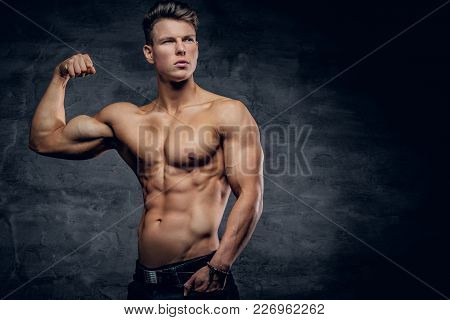 Shirtless Athletic Male Showing Biceps And Posing In A Studio On Grey Background.