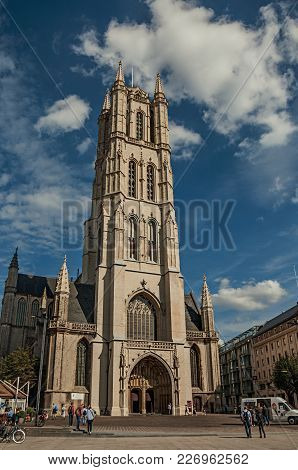 Ghent, Belgium - July 03, 2017. People, Gothic Cathedral And Blue Cloudy Sky In Ghent. In Addition T