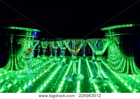 Empty Glasses Of Martini And Wine On The Table With A Bright Green Backlight