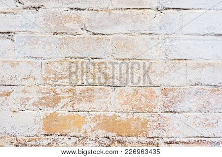 Textured Background Of Old Yellow Brickwork Covered With Cracked And Partially Falling Off Whitewash