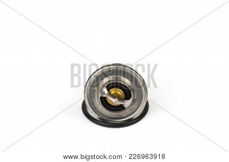 New Car Thermostat On A White Isolated Background Next To A Rubber Gasket. Repair Kit Of Spare Parts