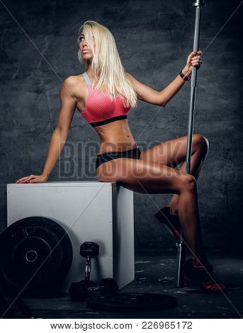 Full Body Studio Portrait Of Slim Blond Female Fitness Model Sits On A Box And Holds Barbell.