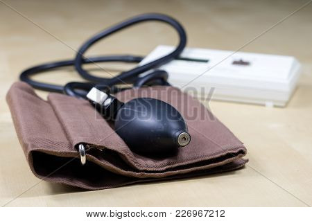 Medical Accessories On A Wooden Table. Stethoscope, And A Medical Sphygmomanometer In The Doctor's O