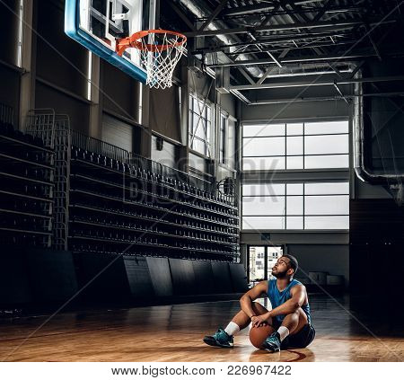 Portrait Of Black Basketball Player Sits On A Floor Under  A Hoop In A Basketball Hall.