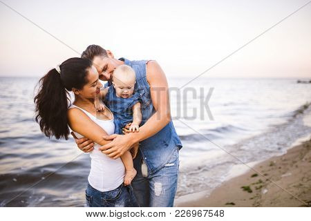 Beautiful Young Family On Vacation With Baby. The Father Holds The Blonde Girl In Her Arms, And The