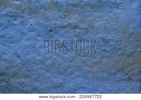 Old Rough Surface Of A Concrete Wall With An Uneven Coating Of Colored Paint