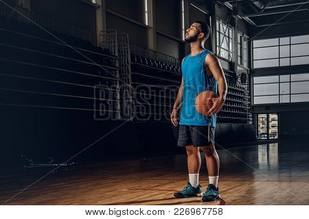 Portrait Of Black Basketball Player Holds A Ball Over A Hoop In A Basketball Hall.