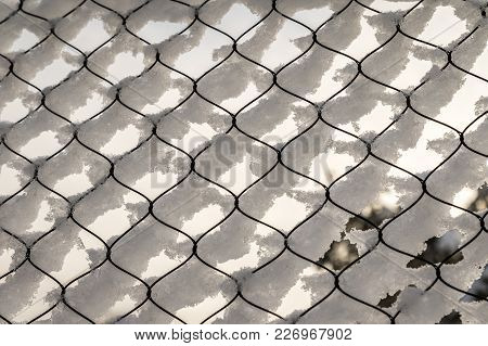 Texture Of Snow On The Fencing Net. Plastic Mesh Covered With Snow In Winter, Soft Background