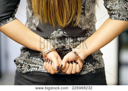 Close-up. Arrested Woman Handcuffed Hands At The Back. Prisoner Or Arrested Terrorist, Hacker, Bribe