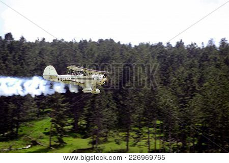 Mende, France - June 25, 2016: Biplane Taking Off, Releasing Smoke From The Mende Airfield In The Fr
