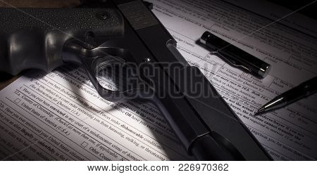 Black Handgun And Background Check Paperwork With Dishonorable Discharge Clause Obvious